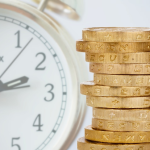 Stack of gold coins on the right side of a clock that symbolizes good money flow.