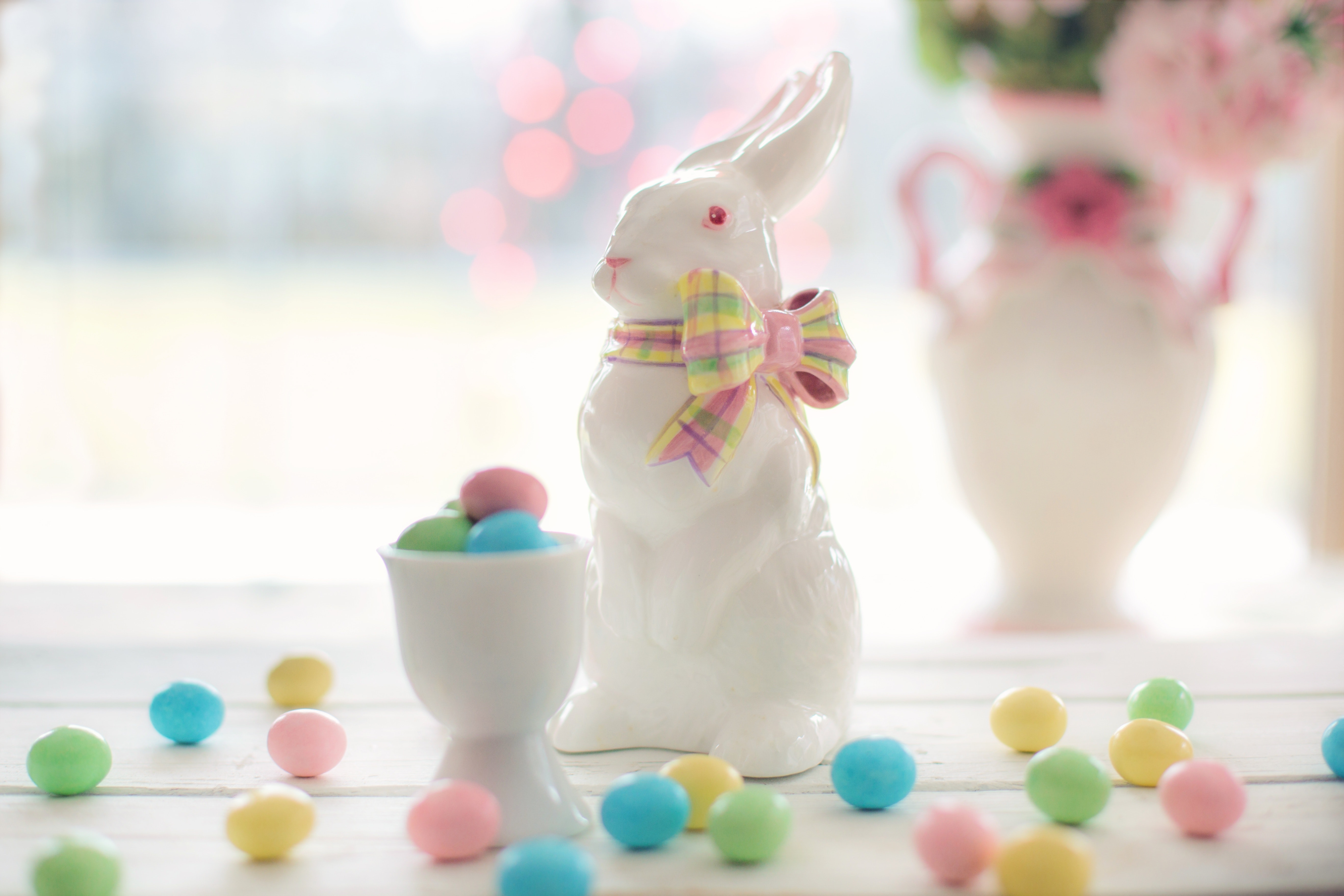 Little easter eggs scattered all over the table and inside a white ceramic.