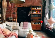 A living room with a brick wall, big glass windows and full of home decoration.