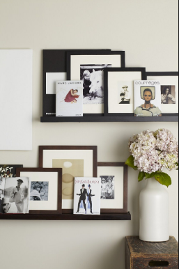 Black picture frames on the white wall.